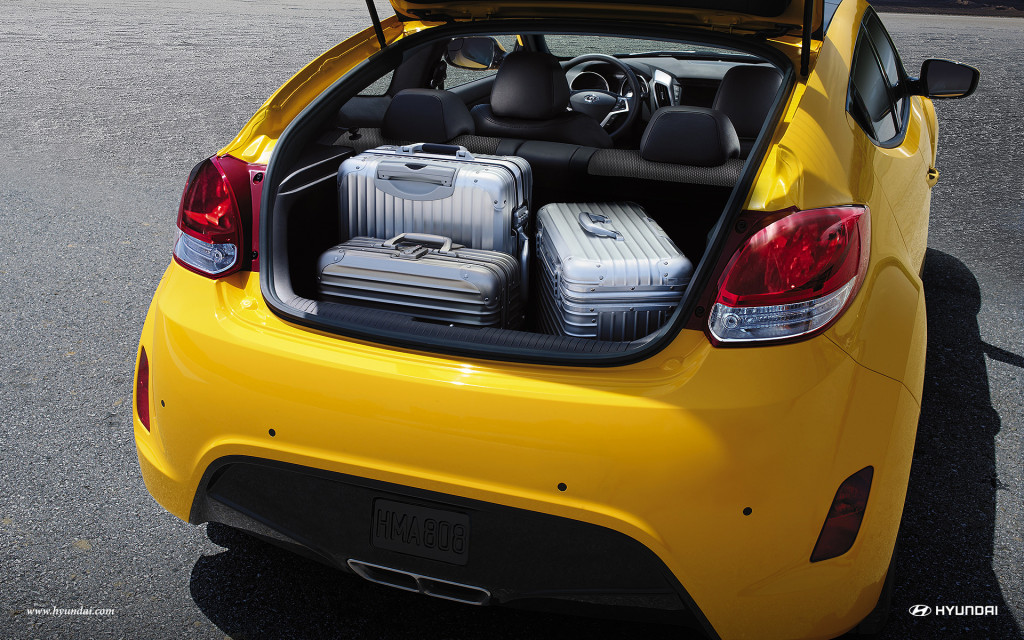 The open trunk of a bright yellow 2016 Hyundai Veloster