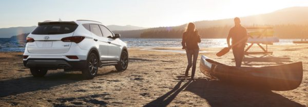 The 2018 Hyundai Santa Fe Sport at the beach, with a couple and a canoe nearby.