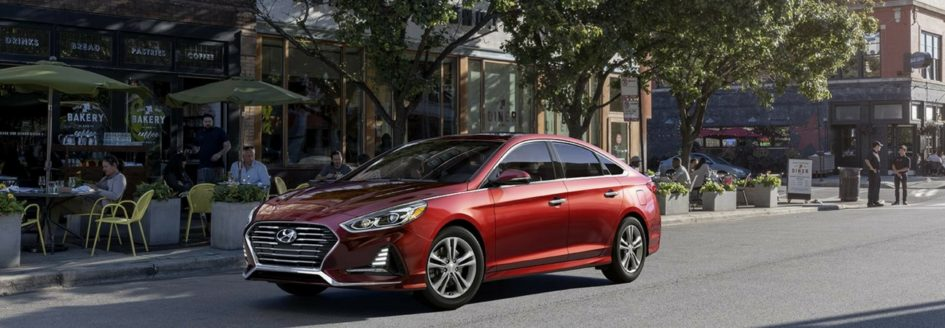 A new Hyundai Sonata driving down the street.