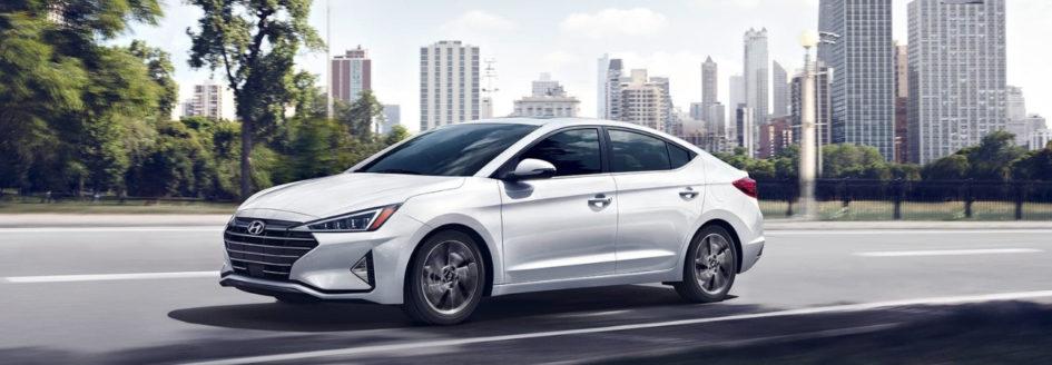 A white 2019 Hyundai Elantra driving down the road