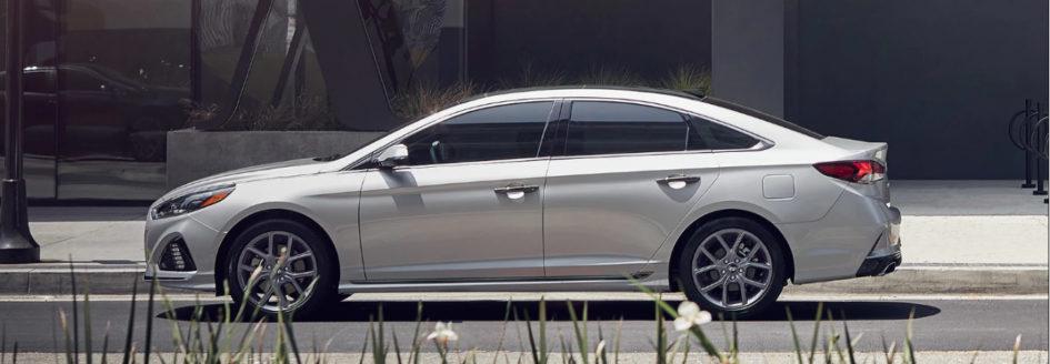 Gray 2019 Hyundai Sonata parked on a city street next to a planter.