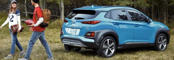 Couple walking away from blue 2020 Hyundai Kona